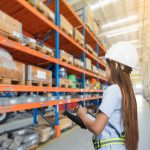 a female worker conducting a pallet racking inspection in London