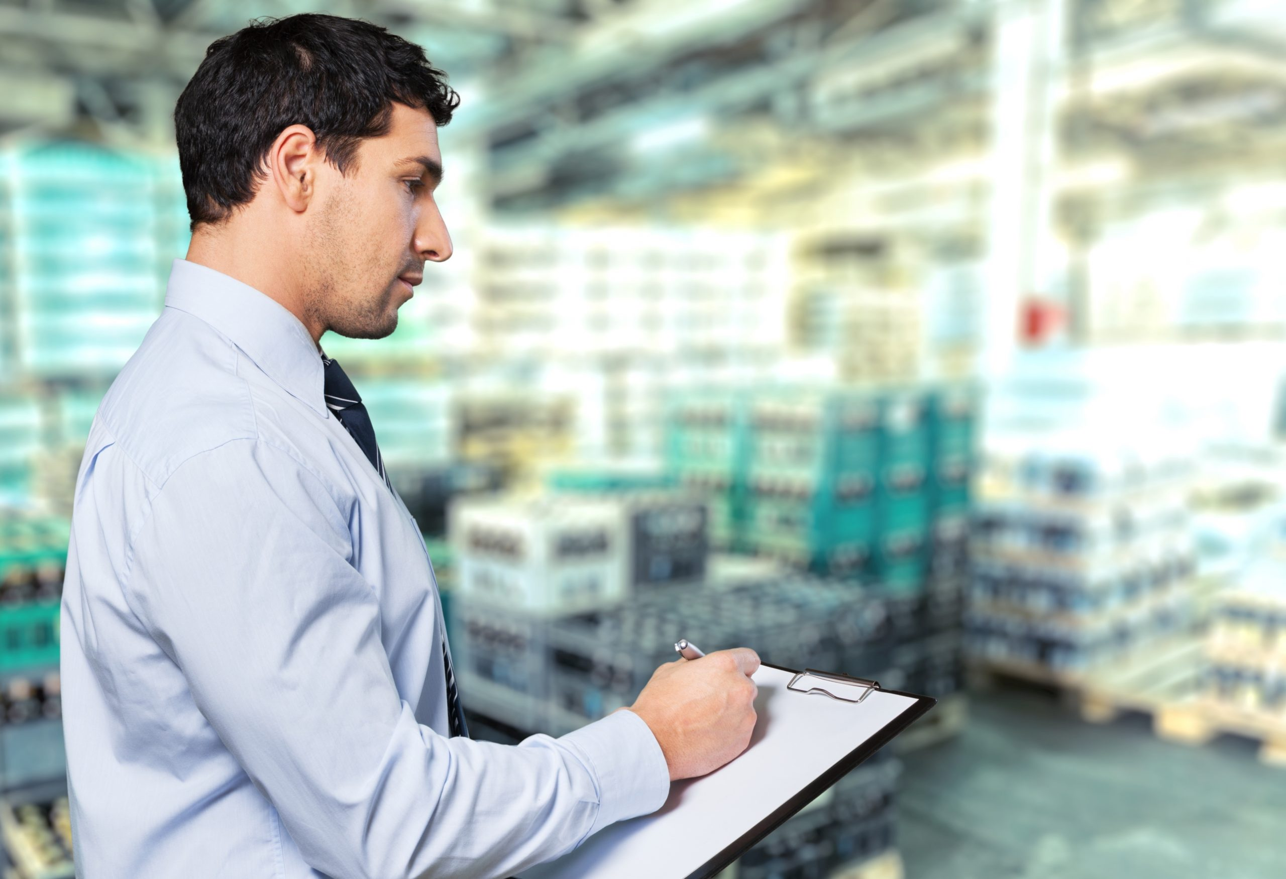 a man in a shirt with a clipboard inspecting a warehouse