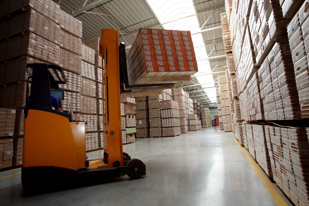 Forklift lifting a box inside a warehouse full of racks with boxes