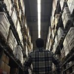 a man looking up at a tall warehouse racking