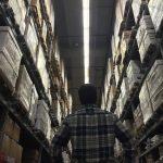a man looking up at a tall warehouse racking