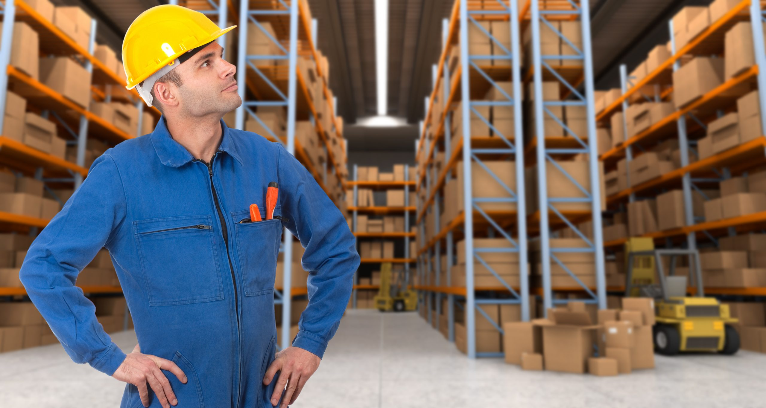 Man with helmet and blue overalls in a warehouse with pallet racking system