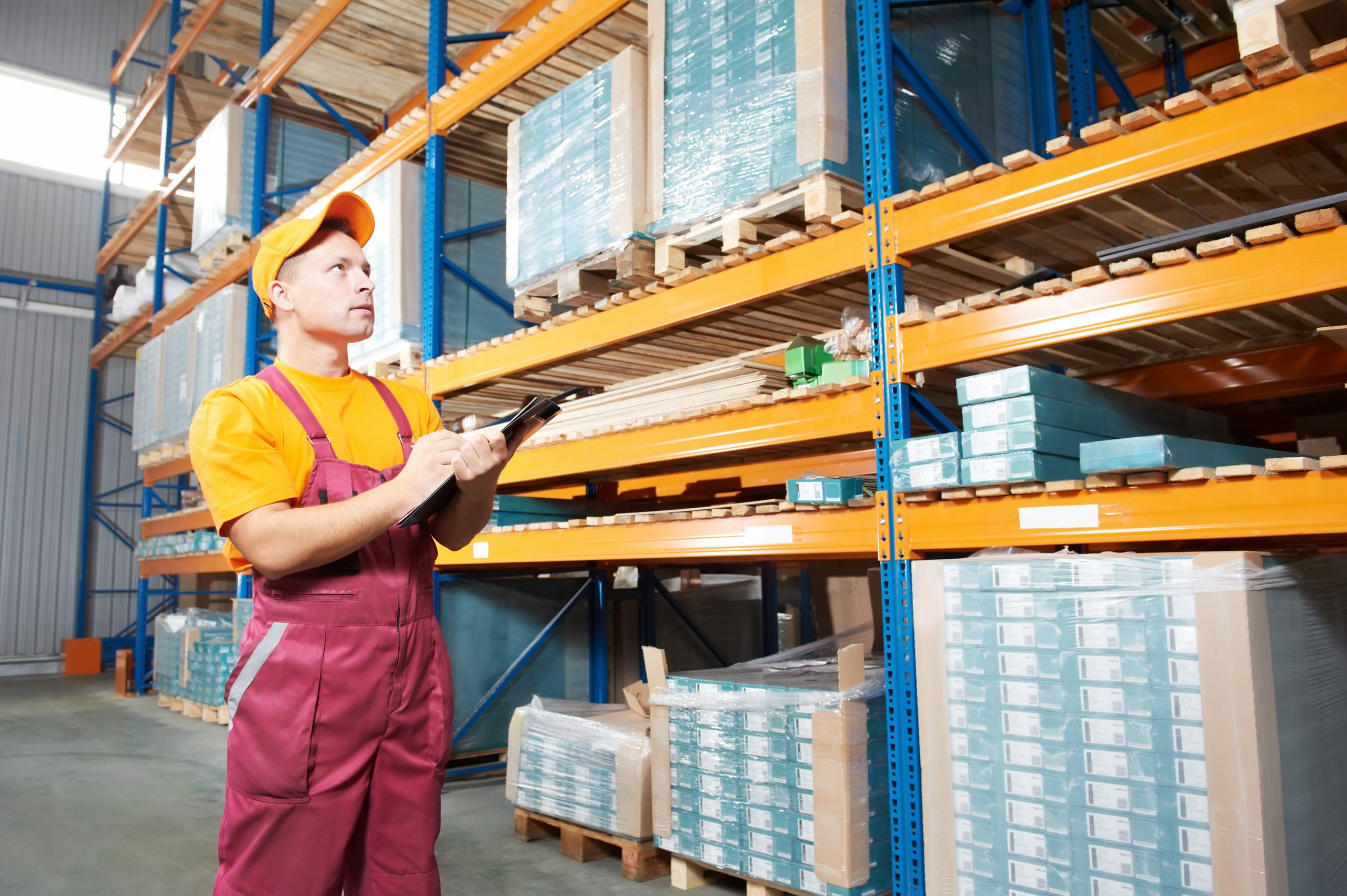 Inspector in uniform doing racking inspection in a warehouse