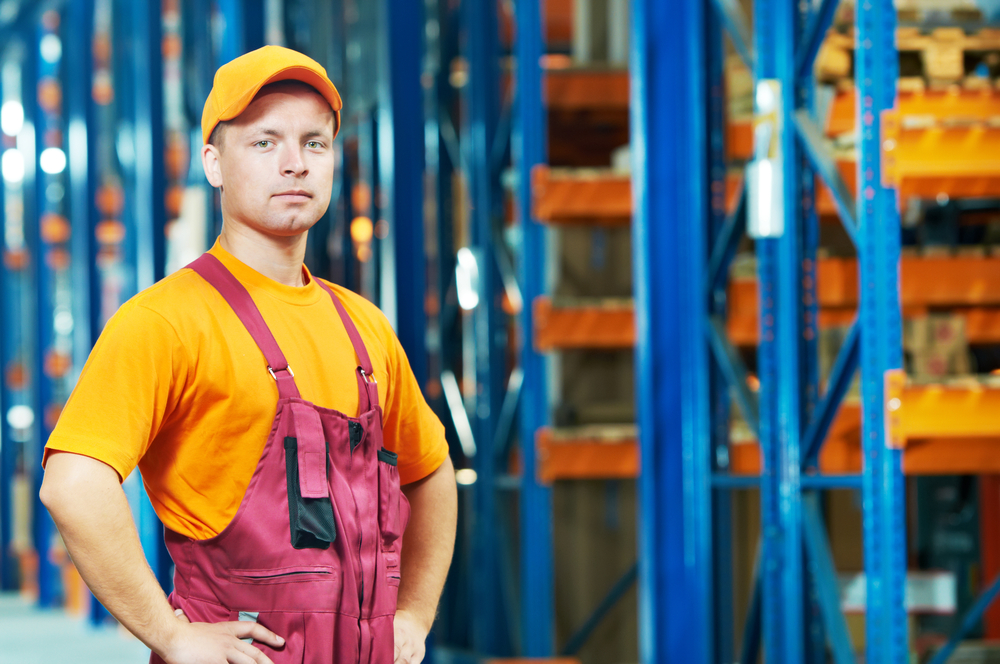 young worker man in uniform in front of warehouse rack arrangement stillages