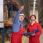 A SEMA approved inspector pointing to warehouse racking