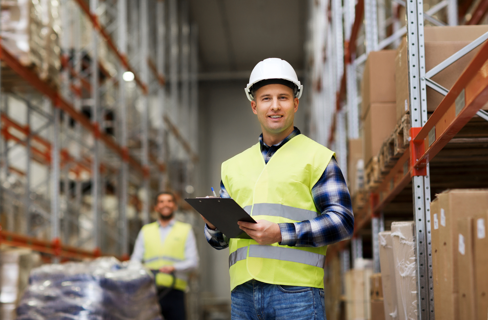 Warehouse racking inspector stands in hard hat with clipboard