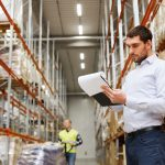 man in warehouse checking racking and load notices